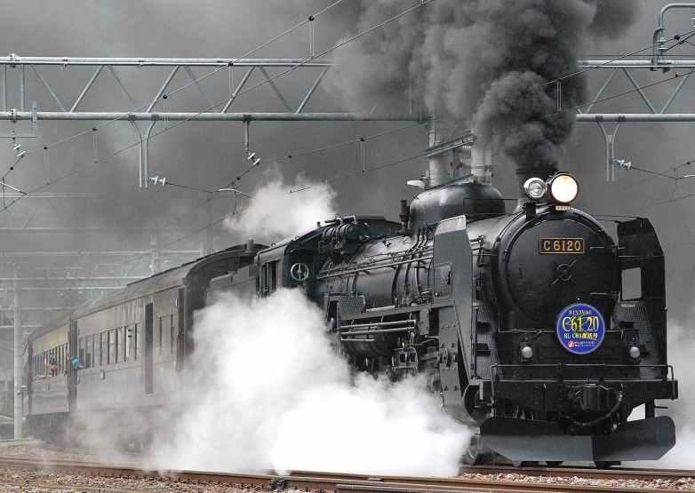 black train on rail and showing smoke